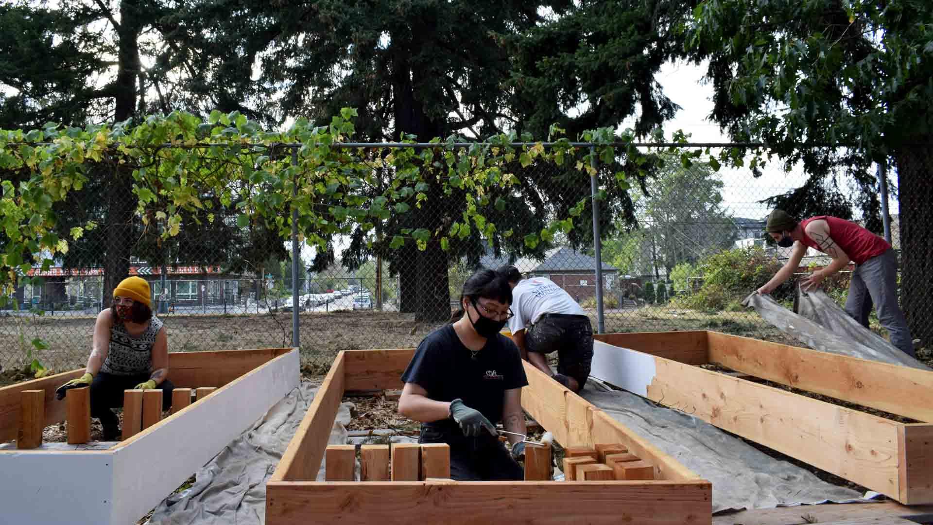 Volunteers construct beds in a community garden