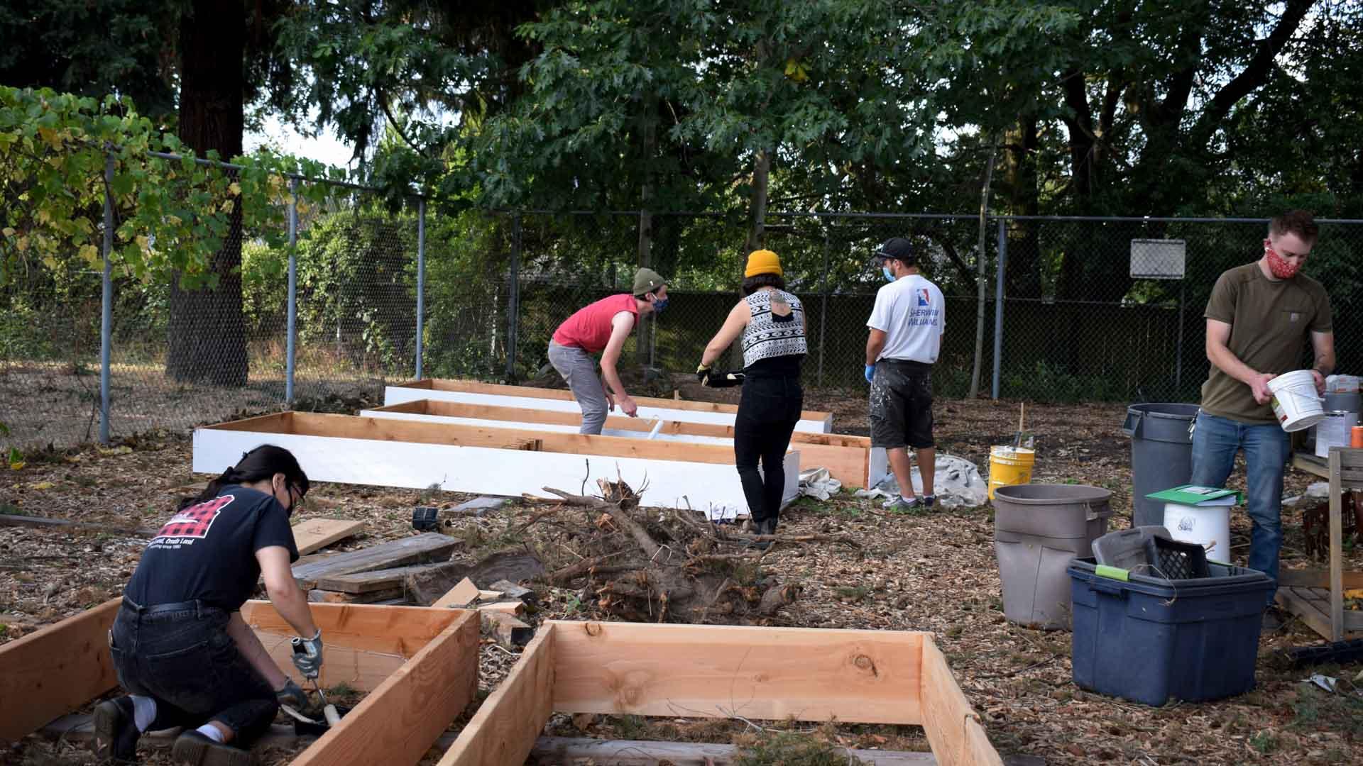 Volunteers construct garden beds